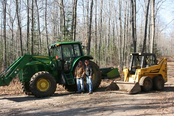 Jim Weyers and Dale Ott pose with our club tractor and Dales Skid Steer after a hard day of picking rocks on Wildwood Trail
