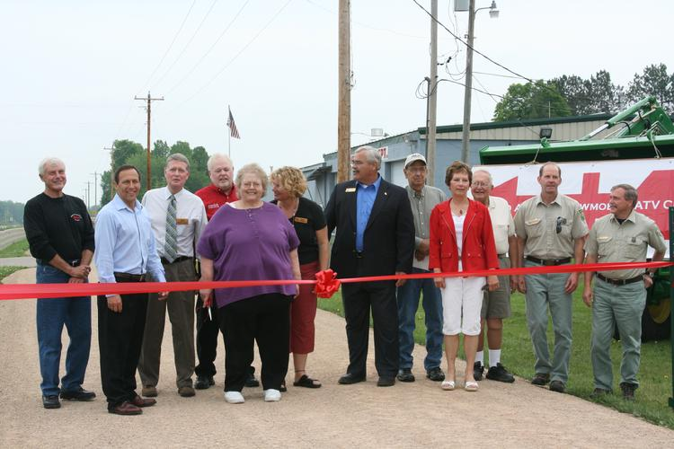 """June 6th 2009 All the speakers were invited to help with the actual ribbon cutting for the new Nicolet State Recreational trail. Sue Rapp, Townsend Chairperson did the honors by cutting the ribbon and declaring the trail open. This """"Multi-Modal"""" trail is open to ATV's, bicycles and foot traffic in the summer and Snowmobiles in the winter. It stretches over 45 miles from south of Gillett to Laona. Next year a five mile stretch north of Laona will open making it possible to ride or bike all the way to the UP."""